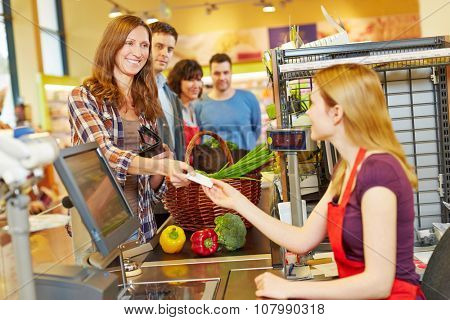 Smiling woman paying with her EC card at supermarket checkout