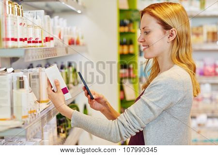 Young smiling woman scanning barcode with smartphone in a drugstore