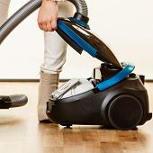 Young woman opening vacuum cleaner on white. Houseworking in home. poster