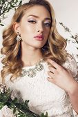 fashion studio photo of gorgeous young woman with blond curly hair wears elegant lace dress and bijou posing among blossom twigs poster