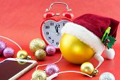 Christmas ball with Santa's hat smartphone with earphones and clock on red poster