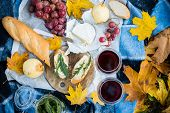 A cozy autumn picnic in the park: fresh bread and cheese, fruit and wine on warm plaid in yellow autumn leaves. Food for dinner outdoors. poster