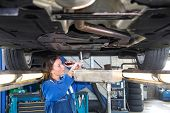 Fremale mechanic chaning the oil of a vehicle on a car lift, using a torque wrench to unscrew the oil tank. A collection vessel is placed underneath the outlet for environmental and recycling purposes poster