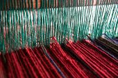 Wool yarn on a loom at an Arab Bedouin women's craft cooperative in the township of Lakiya, Israel. poster