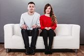 Shy woman and man sitting on sofa couch next each other. First date. Attractive girl and handsome guy meeting dating and trying to talk. poster