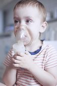 a child in a mask by a nebulizer for inhalation during asthmatic attack. medical therapy if difficulty breathing, asthma, respiratory diseases poster