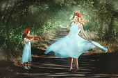 Little girl playing the violin and an adult woman is dancing. They are in the woods and are like at the fabulous fairies. poster