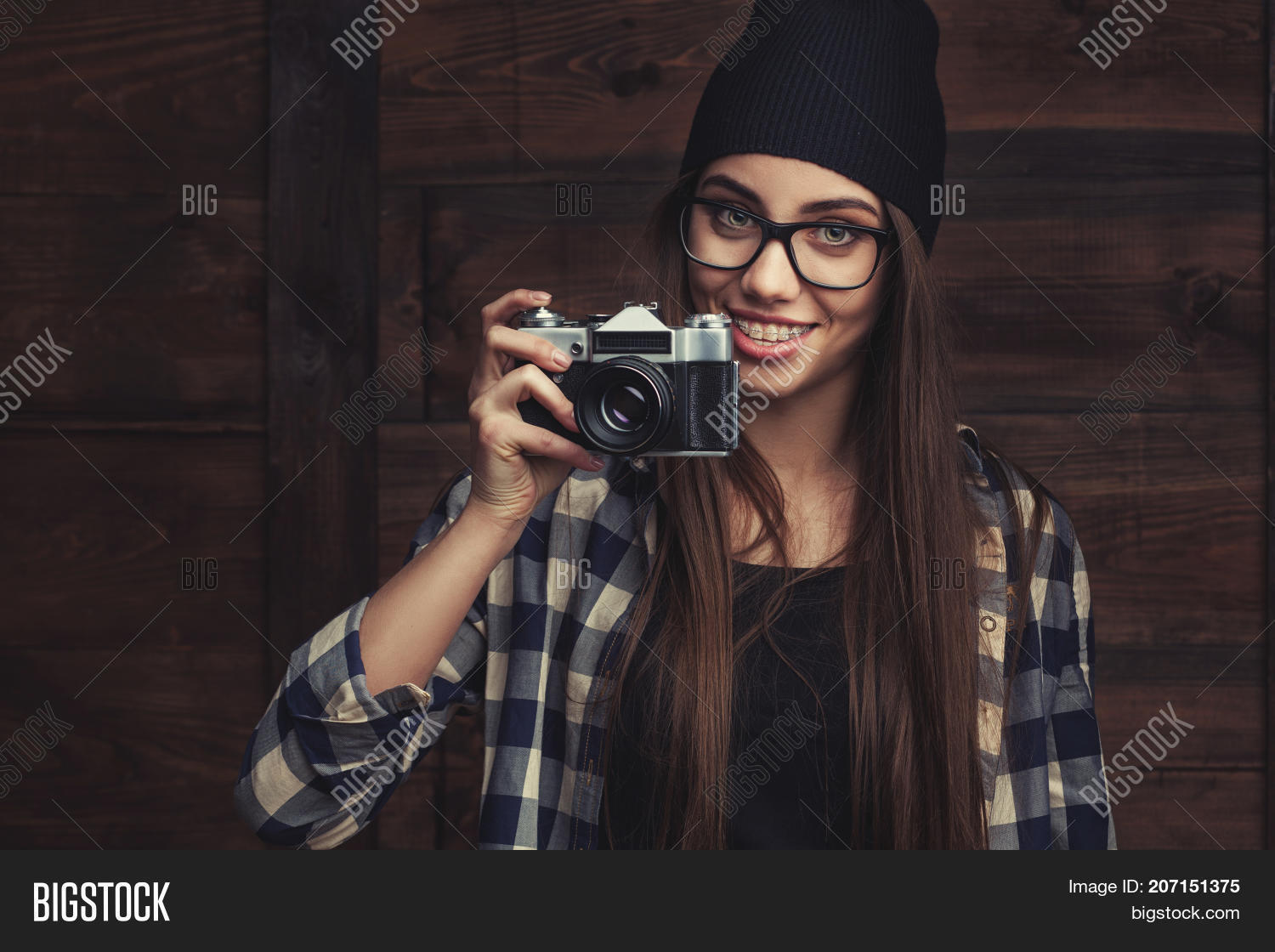 54ba8c176da Smiling Hipster girl in glasses and black beanie with vintage camera on the  wooden background
