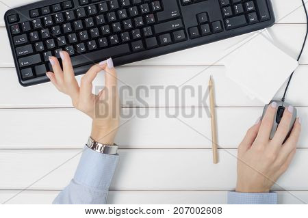 Female hands gesture okey notes for notes keyboard mouse from computer on white wooden background isolation