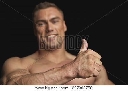 Fitness Trainer Showing Big Thumb on Black Background