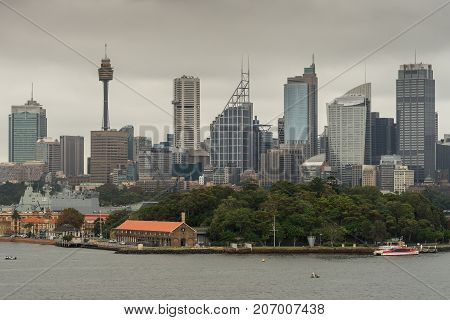 Sydney Australia - March 21 2017: Green trees of Garden Island in front of city skyline section with Eye tower under gray sky. Shot from the bay: people on shore line boats and buoys.