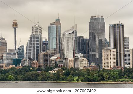 Sydney Australia - March 21 2017: Green trees of Botanical garden in front of city skyline section under gray sky. Shot from the bay: people on shore line and Sydney Eye tower.