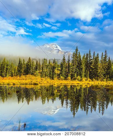 Indian summer. The Patricia Lake reflects the snowy peak of the Pyramid Mountain. The concept of extreme and ecotourism