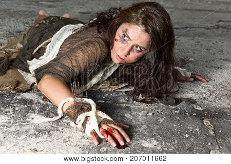Young abused and frightened woman sitting on the floor of a derelict building