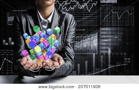 Cropped image of business woman in suit presenting multiple cubes in hands as symbol of innovations. Business sketches on background. 3D rendering.