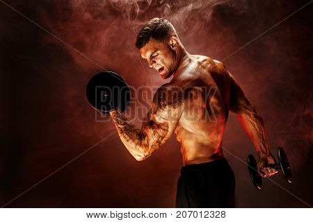 Very brawny guy bodybuilder. Portrait of roaring muscular man lifting dumbbell in red smoke. Studio shot.