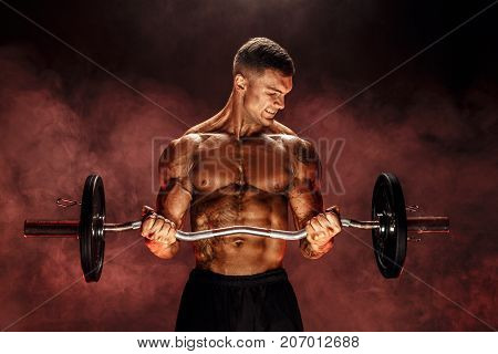 Studio portrait of topless bodybuilder performing biceps exercise with concentrated face over black background with smoke. Cutout. Very brawny guy bodybuilder.