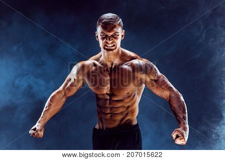 Very brawny guy bodybuilder posing. Beautiful sporty guy male power. Fitness muscled man. Roar. Smoke cold background.