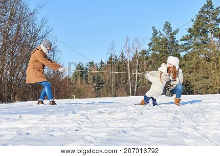 Family with child having fun in the snow and playing tug of war