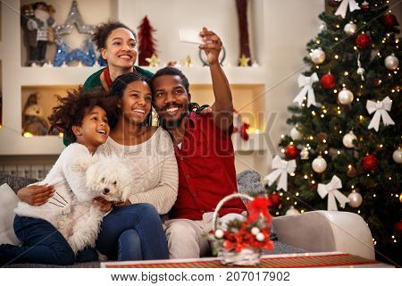 Cheerful African family making selfie together for Christmas