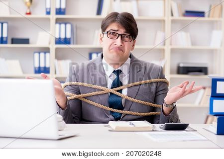 Businessman tied up with rope in office
