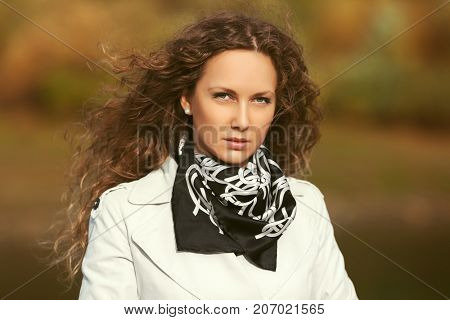 Beautiful fashion woman in white trench coat walking in autumn park. Stylish female model with long curly hairs outdoor