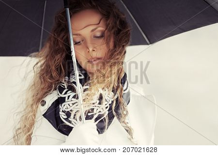 Beautiful fashion woman in white trench coat walking in city street. Stylish female model with umbrella outdoor
