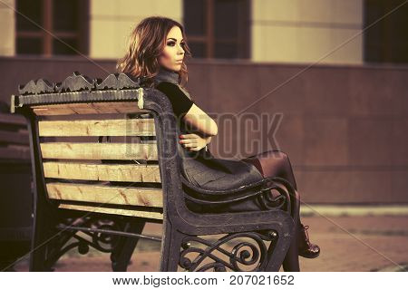 Young woman with long curly hairs sitting on bench in city street. Stylish fashion model in long vest outdoor
