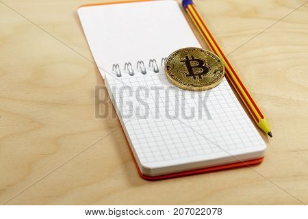 The cryptocurrency bitcoin coin on open notepad.Business concept
