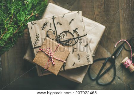 Preparing for Christmas or New Year holiday. Flat-lay of gift boxes, green fur tree branches, rope, scissors over rustic wooden table background, top view
