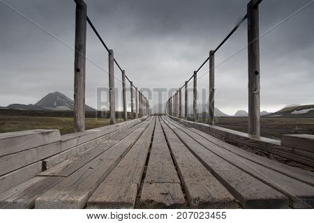 A grey wooden bridge in Iceland with background
