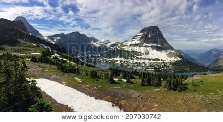 Going to the Sun Road, View of Landscape, snow fields In Glacier National Park around Logan Pass, Hidden Lake, Highline Trail, which features waterfalls, wildlife, and is surrounded by mountains including: Piegan, Pollock, Oberlin, Clements, Reynolds and