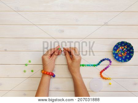 Woman making colored beads. Polymer clay. Background of white wood.