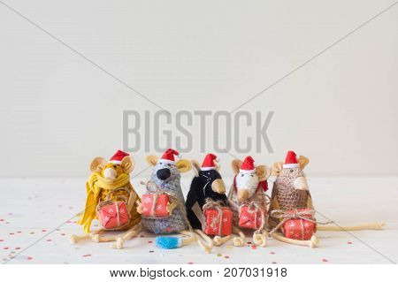 Homemade toy mouse in Christmas hats. Mouse in the paws holding gifts. Beige background.