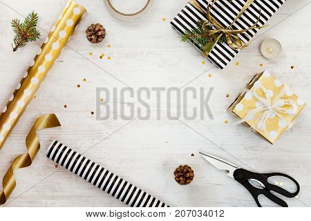 Gift boxes wrapped in black and white striped and goden dotted paper with pine cones candle and wrapping materials on a white wood old background. Christmas presents preparation. Empty space.