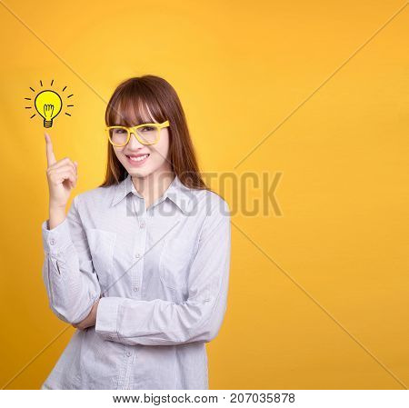 Business Asian woman with yellow vintage glasses stand and have idea lamp bulb light on fingertip yellow background with copy space for design for poster and advertising text. Asia model in her 20s.