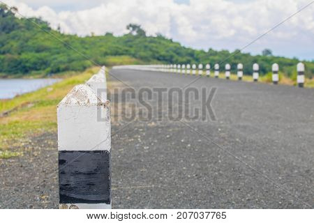 Black and white mileposts on a road near river