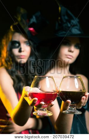 Halloween party 2017 Fashion women like witch holding cocktail of blood. Scary makeup. Hallowen costumes. Role. Witch carnival costume
