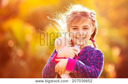 Portrait of a cute little girl holding in hands her favorite precious doll, playing outside, over natural orange background, pretty child playing mother's daughters in warm autumn day