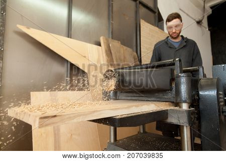 Young skilled carpenter in protective eyewear operating stationary planer machine in small shop, working with wooden plank, making shredded wood as a result of trimming boards to consistent thickness