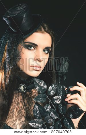 Queen young woman holding black rose, Halloween party 2017 Beautiful woman like doll with hat. Halloween costumes. Role. Witch carnival costume. Sexy girls. Night club