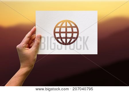 Female Hand Holding Globe Perforated Paper Craft In Mountain Background