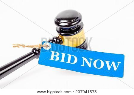 Bid now text on paper tag with wooden gavel auction isolated on white background.