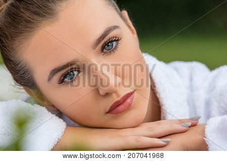 Beautiful girl or young woman relaxing in robe outside at health spa