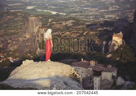 Alone girl in a red dress and scarf standing on the edge of the rock and prays at the monasteries of Meteora. Female on the rock and monasteries of Meteora in Greece in Thessaly