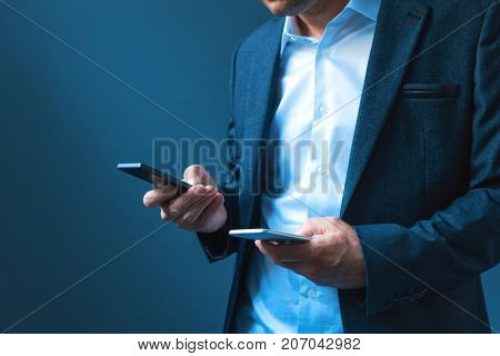 Sync and backup data on two mobile phones man in business suit synchronizes files messages and contact information on private and company smartphones