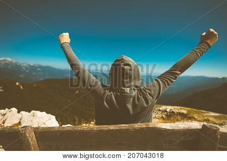 Success triumph and victory. Victorious female person standing on mountain top with arms raised in V. Achievement and accomplishment in life. Toned image.