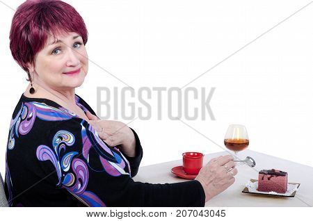 Adult mature woman in colored dress sits at white table and begs to allow her to eat high-calorie cake