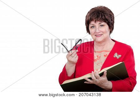 Aged female professor in red jacket posing with big book in left hand and glasses in right