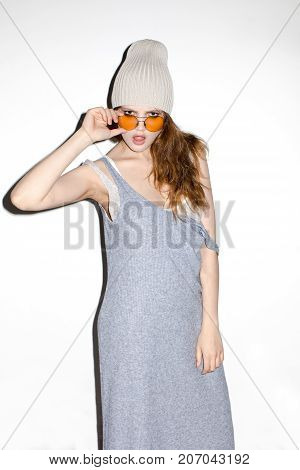 Young trendy model in casual dress and hat touching sunglasses looking provocatively at camera.